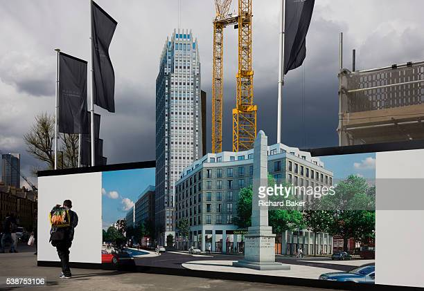A pedestrian walks past a hoarding showing the future skyscraper being built by housing developer Barratt at Blackfriars Circus at the southern end...