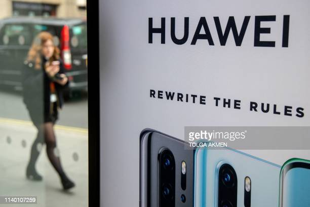 A pedestrian walks past a Huawei product stand at an EE telecommunications shop in central London on April 29 2019 British Foreign Secretary Jeremy...