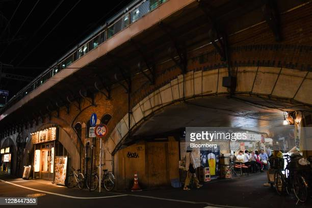 Pedestrian walks past a izakaya restaurant built under railway tracks in Tokyo, Japan, on Tuesday, Sept. 8, 2020. In Tokyo, the spaces beneath...