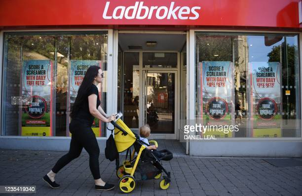 Pedestrian walks past a Ladbrokes betting shop in east London on September 22, 2021. - UK gambling giant Entain said on Wednesday it had received a...