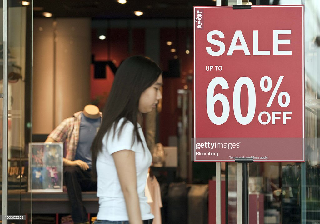 A pedestrian walks past a Levi's store advertising a sale in Singapore, on Monday, May 24, 2010. Singapore's consumer prices rose at the fastest pace in 14 months in April as an accelerating economy and a booming labor market boosted housing and transportation costs. Photographer: Charles Pertwee/Bloomberg via Getty Images