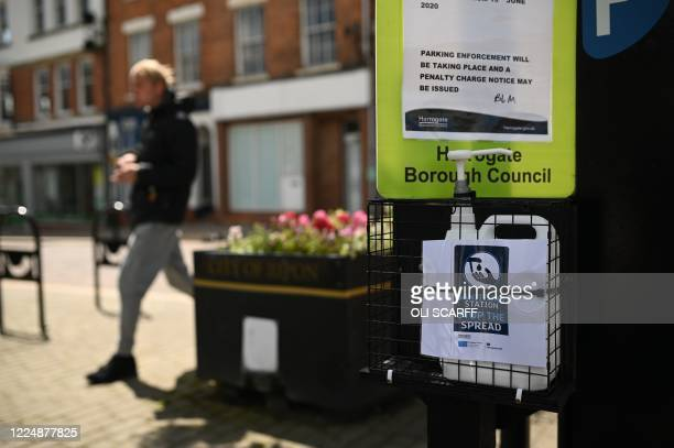 Pedestrian walks past a local council hand sanitizer station in the street in Ripon, north Yorkshire, on July 5 during the novel coronavirus COVID-19...