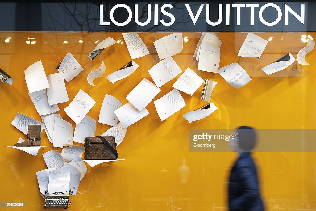 A pedestrian walks past a Louis Vuitton store, operated by LVMH Moet Hennessy Louis Vuitton SA, in the Ginza district of Tokyo, Japan, on Sunday, Jan. 20, 2013. Japan's consumer prices excluding fresh food, a benchmark monitored by the central bank, haven't advanced 2 percent for any year since 1997, when a national sales tax was increased. Photographer: Kiyoshi Ota/Bloomberg via Getty Images
