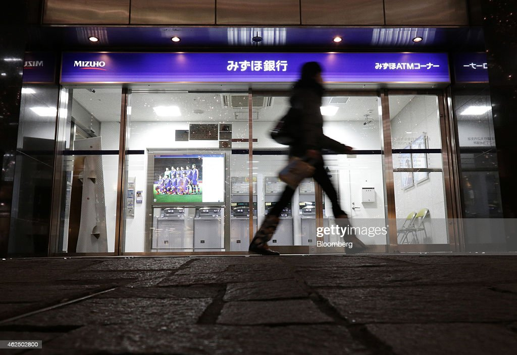 A pedestrian walks past a Mizuho Bank Ltd. branch in Tokyo, Japan, on Thursday, Jan. 29, 2015. Mizuho Financial Group Inc., Japan's third largest bank, is scheduled to report third-quarter earnings on Jan. 30. Photographer: Tomohiro Ohsumi/Bloomberg via Getty Images