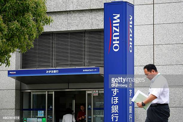 A pedestrian walks past a Mizuho Bank Ltd branch in Tokyo Japan on Tuesday May 13 2014 Mizuho Financial Group Inc Japan's third largest bank is...