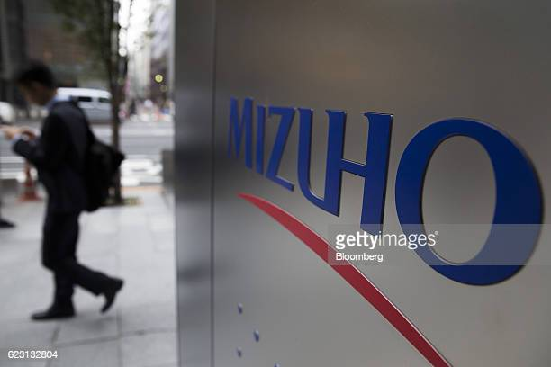A pedestrian walks past a Mizuho Bank Ltd branch in Tokyo Japan on Monday Nov 14 2016 Mizuho Financial Group Incs secondquarter profit beat analysts...