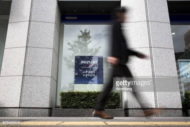 A pedestrian walks past a Mizuho Bank Ltd branch in Tokyo Japan on Friday Nov 10 2017 Mizuho Financial Group Japan's third largest lender is...