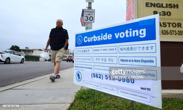 A pedestrian walks past a multilanguage voting sign posted near a polling station in Monterey Park Los Angeles County California on June 5 2018 as...