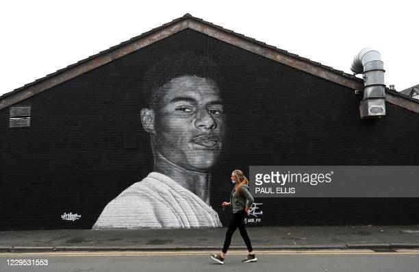 Pedestrian walks past a mural by grafitti artist Akse P19 of Manchester United football player Marcus Rashford on teh side of a building in...