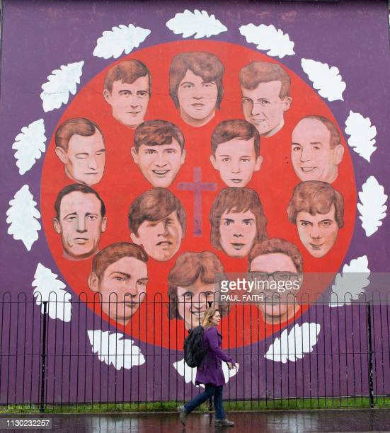 TOPSHOT A pedestrian walks past a mural commemorating the victims of the 1972 Bloody Sunday killings in the Bogside area of Derry Northern Ireland on...