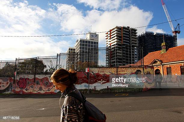 A pedestrian walks past a mural featuring Aboriginal dot painting on Eveleigh Street in the inner city suburb of Redfern in Sydney Australia on...