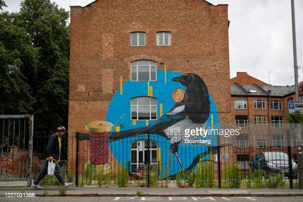 A pedestrian walks past a mural of a magpie on a former textile business in Leicester UK on Monday July 13 2020 Leicester has been a hub for...