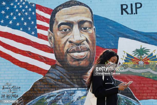 Pedestrian walks past a mural painted by artist Kenny Altidor depicting George Floyd on a sidewall of CTown Supermarket on March 9, 2021 in the...