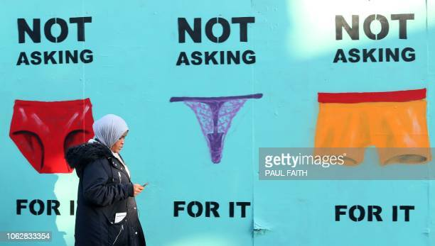 A pedestrian walks past a mural showing pictures of underwear with the slogan 'Not Asking For It' in a street in Dublin on November 17 2018 as a...