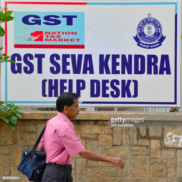 A pedestrian walks past a poster advertising about the new goods and services tax regime at the Service Tax Office in Bangalore on June 29 2017 India...