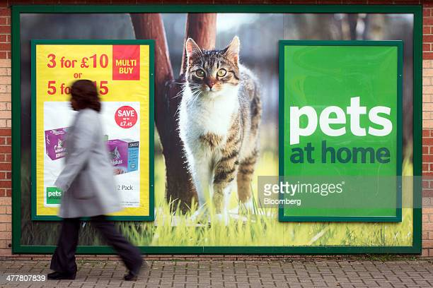 A pedestrian walks past a poster of a cat outside a Pets at Home Ltd store in London UK on Monday March 10 2014 Pets at Home majorityowned by...