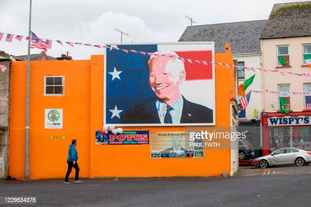 Pedestrian walks past a poster showing support to US president-elect Joe Biden in his ancestral hometown of Ballina in County Mayo in northwest...