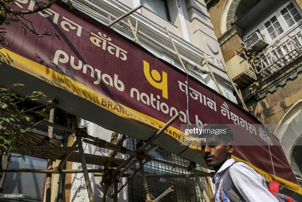 A pedestrian walks past a Punjab National Bank branch in Mumbai India on Wednesday Feb 14 2018 PNB one of India`s biggest banks has accused...