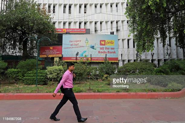 A pedestrian walks past a Punjab National Bank office building in New Delhi India on Monday July 8 2019 India's beleaguered staterun lenderPNB...