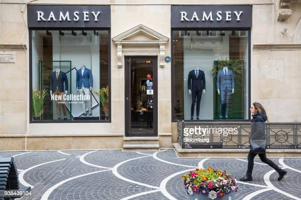 A pedestrian walks past a Ramsey clothing store in Baku Azerbaijan on Friday March 16 2018 Azerbaijan's economy barely returned to growth last year...