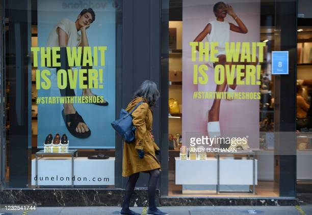Pedestrian walks past a re-opened shoe shop in Glasgow on April 26, 2021 following the relaxing of some Covid-19 restrictions in Scotland, after the...