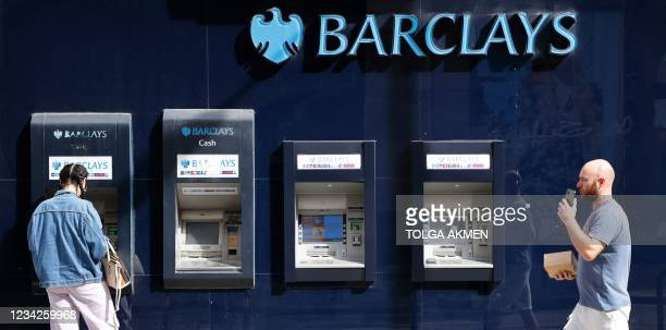 Pedestrian walks past a row of ATMs as a customer uses one outside a branch of British bank Barclays in central London on July 28, 2021. - British...