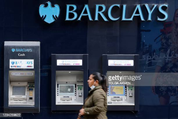 Pedestrian walks past a row of ATMs outside a branch of British bank Barclays in central London on July 28, 2021. - British bank Barclays said...