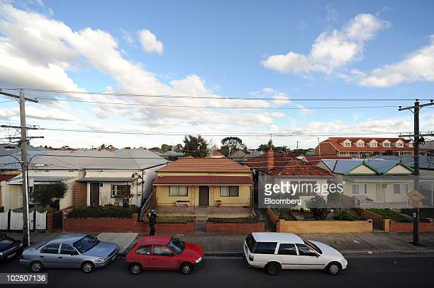 Pedestrian walks past a row of bungalow houses in Brunswick, a northern suburb of Melbourne, Australia, on Monday, June 28, 2010. A shortage of...