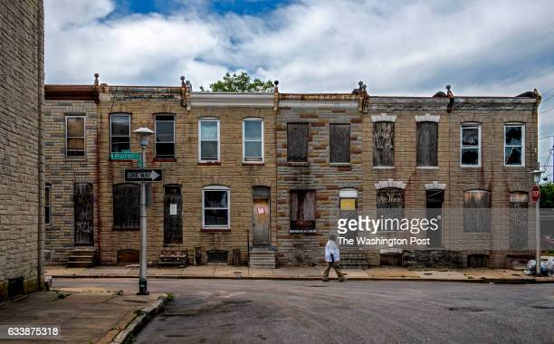 A pedestrian walks past a row of houses on N Bradford street slated for demolition on June 2016 in Baltimore MD