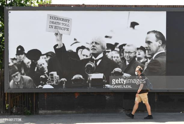 A pedestrian walks past a satirical billboard showing Britain's Prime Minister Boris Johnson superimposed on the face of Britain's World War II...