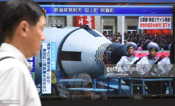 A pedestrian walks past a screen in Tokyo on July 4 2017 broadcasting file news footage of a military parade showing North Korean soldiers and a...