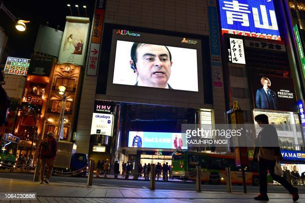 A pedestrian walks past a screen showing a news programme featuring Nissan chairman Carlos Ghosn in Tokyo on November 22 2018 Top executives from...