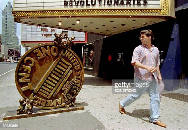 Pedestrian walks past a sculpture of a giant penny on New York's 42nd Street 9 July 1993 as two dozen artists, architects and designers transform a...