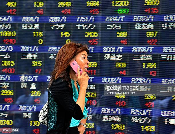 A pedestrian walks past a share prices board in Tokyo on September 13 2011 Japan's stocks prices rose 8088 points to close at 861655 points at the...