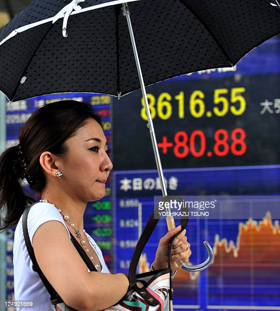 A pedestrian walks past a share prices board in Tokyo on September 13 2011 Japan's stock prices rose 8088 points to close at 861655 at the Tokyo...