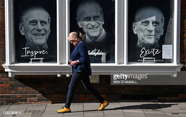 Pedestrian walks past a shop displaying images of Britain's Prince Philip, Duke of Edinburgh, in Windsor, west of London, on April 13 following his...