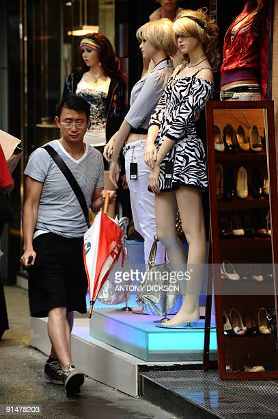 A pedestrian walks past a shop selling clothing in Hong Kong on September 29 2009 According to statistics released by the government the value of...