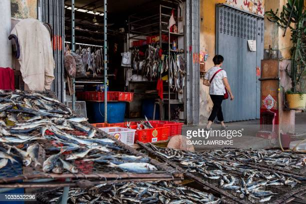 A pedestrian walks past a shop selling dried fish before the expected arrival of Super Typhoon Mangkhut in Macau on September 15 2018