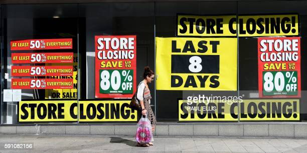 A pedestrian walks past a shop with a closing down sale promotion in Liverpool north west England on August 17 2016 From computers and cars to...