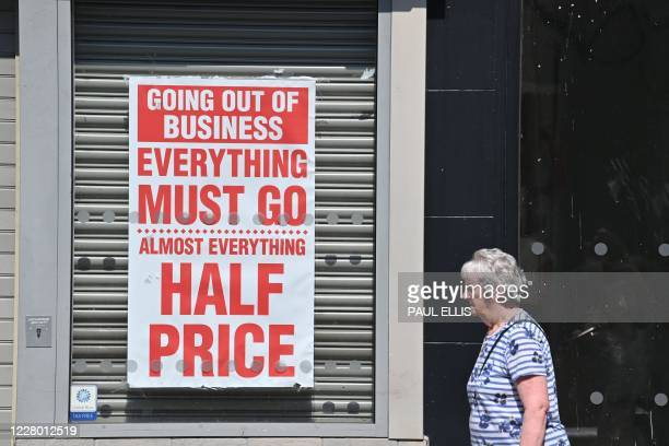 Pedestrian walks past a shuttered jewellery store with a closing down sale poster in the window in Chester, northwest England on August 12, 2020. -...