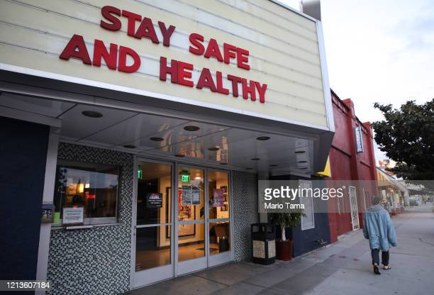 Pedestrian walks past a shuttered movie theater, with the message 'Stay Safe and Healthy' displayed on the marquee, on March 19, 2020 in Los Angeles,...