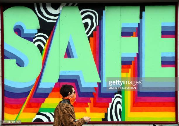 "Pedestrian walks past a shuttered restaurant with a mural that reads ""Stay Safe"" on it in Glasgow on May 16 during the novel coronavirus COVID-19..."
