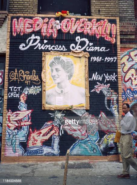 Pedestrian walks past a sidewalk mural, 'Media Overkill!' , in tribute to Princess Diana, on a wall in the East Village neighborhood, New York, New...