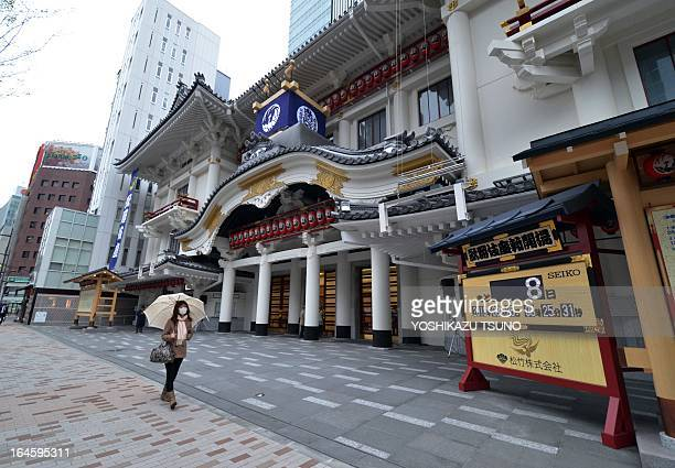 A pedestrian walks past a sign board that says eight more days until the opening the recently rebuilt kabuki art theatre in Tokyo on March 25 2013...