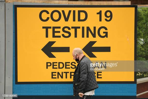 Pedestrian walks past a sign directing members of the public to a Covid-19 testing centre in Bolton, northwest England, on May 28, 2021. - British...