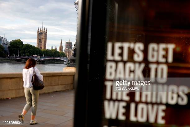 A pedestrian walks past a sign encouraging us to get back to the things we love on the southbank with the Palace of Westminster behind in London on...