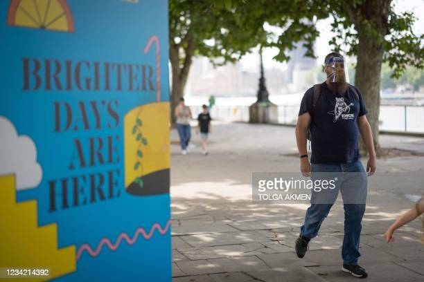 Pedestrian walks past a sign on the southbank in central London on July 26, 2021. - For the first time in the latest wave of coronavirus covid-19...