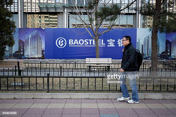 A pedestrian walks past a sign outside the Baosteel Group Corp building under construction in Beijing China on Tuesday March 24 2009 Baoshan Iron...
