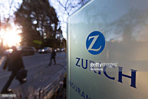 A pedestrian walks past a sign outside the Zurich Insurance Group AG's headquarters ahead of the company's full year results news conference in...