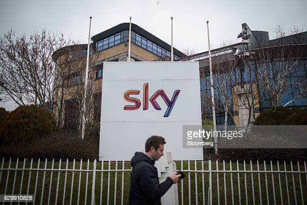 A pedestrian walks past a 'Sky' logo sign outside Sky Plc headquarters in Isleworth London UK on Thursday Dec 15 2016 21st Century Fox Inc may...